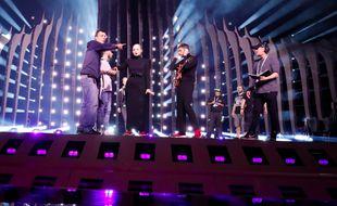 Vêtus de noir et chaussés de rouge, Emilie Satt et Jean-Karl Lucas écoutent les indications de l'équipe technique avant leur première répétition sur la scène de l'Eurovision, à Lisbonne, le 4 mai 2018.