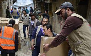 Des travailleurs humanitaires apportent de l'aide alimentaire dans le camp de réfugiés de Yarmuk près de Damas, le 11 mars 2015