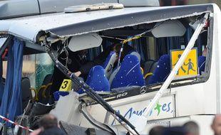 La ridelle qui s'est détachée du camion a scié une partie du car scolaire. / AFP / XAVIER LEOTY