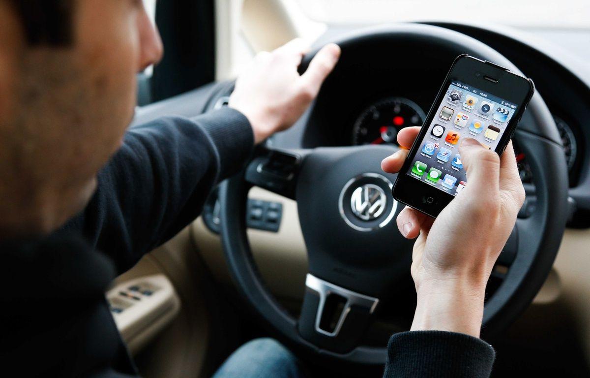 Un homme avec un téléphone au volant de sa voiture. Illustration. –  ISOPIX / Sipa