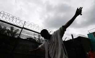 Un migrant lève les mains au ciel près des barbelés qui entourent le centre d'hébergement Emmaüs où il réside, le 4 août 2015 à Vincennes