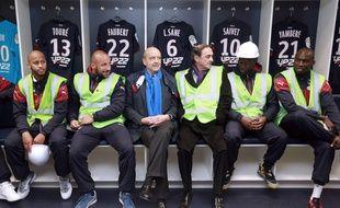 Le Maire de Bordeaux, Alain Juppé, aux côtés du président des Girondins, Jean-Louis Triaud et entouré des joueurs du club, dans les vestiaires du Nouveau stade de Bordeaux, le 23 mars 2015. AFP PHOTO / NICOLAS TUCAT