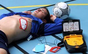 Une personne pose des électrodes d'un défibrillateur externe automatique (DEA) sur un jeune homme