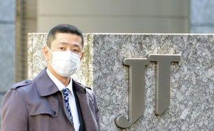 Un passant devant le siège de Japan Tobacco à Tokyo le 15 mars 2013