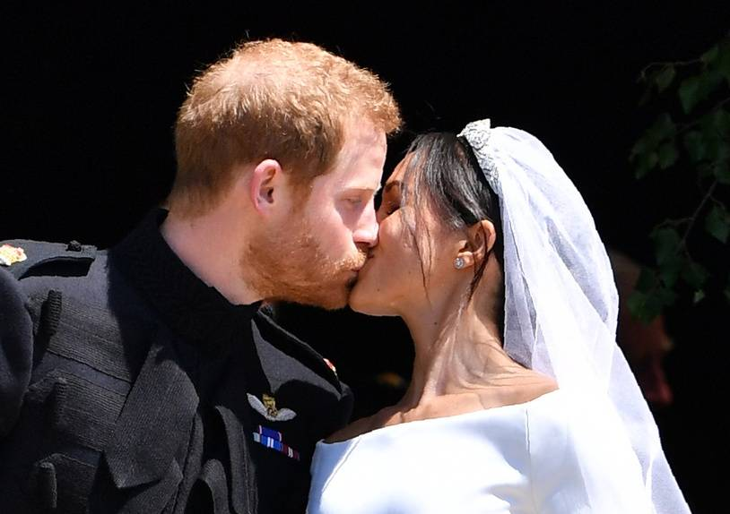 Britain's Prince Harry, Duke of Sussex kisses his wife Meghan, Duchess of Sussex as they leave from the West Door of St George's Chapel, Windsor Castle, in Windsor, on May 19, 2018 after their wedding ceremony. / AFP PHOTO / POOL / Ben STANSALL