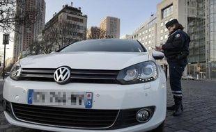 Un policier contôle un automobiliste le 23 mars 2015 à Paris où la circulation alternée est entrée en vigueur