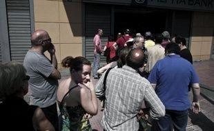 Des Grecs font la queue pour retirer de l'argent dans un distributeur, le 28 juin 2015 à Athènes