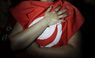 Illustration d'un drapeau tunisien dans les bras d'une femme.