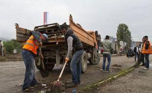 A Mitrovica, des ouvriers retirent une barricade installée il y a trois ans pour empêcher l'accès des Kosovars albanais, le 18 juin 2014