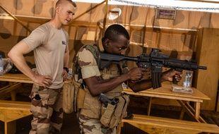 Un soldat français de Barkhane apprend à un soldat des forces armées maliennes l'utilisation de son arme, le 27 avril 2019.