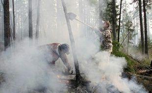 Des pompiers tentent d'étteindre un feu dans la taïga sibérienne en Russie, le 29 août 2015 près de la ville d'Irkutsk
