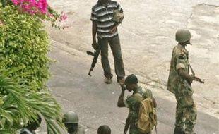 Des partisans du président sortant, Laurent Gbagbo, contrôlent un homme à proximité du palais présidentiel, hier à Abidjan.