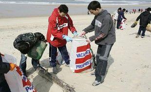 Des élèves du collège Capeyron de Mérignac ramassent des détritus sur la plage sud de Lacanau-Océan, le 17 mars 2006, lors d'une opération de collecte des déchets organisée par Surfrider Foundation Europe.