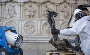 Un ouvrier en train de nettoyer un débris après l'incendie de Notre-Dame