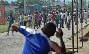 Un manifestant hostile à un 3e mandat de Pierre Nkurunziza lance une pierre en direction de membres de l'aile pour la jeunesse du parti au pouvoir, dans une banlieue de Bujumbura, le 25 mai 2015