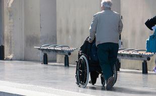 Un voyageur handicapé et son accompagnant sur un quai de gare. (Illustration)
