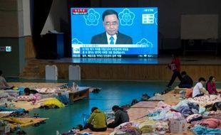Les proches des disparus duSewol regardent l'allocution télévisée au cours de laquelle le Premier ministre sud-coréen annonce sa démission, le 27 avril.