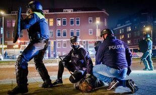 Des policiers néerlandais arrêtent un émeutier anti-couvre-feu le 25 janvier 2021 à Rotterdam, aux Pays-Bas.