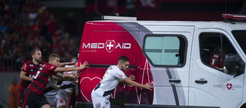 Les Brésiliens Everton Ribeiro (à gauche), Piris da Motta (à droite) et le Brésilien Vasco da Gama, Andrey (R), et d'autres coéquipiers des deux équipes poussent l'ambulance transportant le joueur blessé de Vasco da Gama, Bruno Silva.