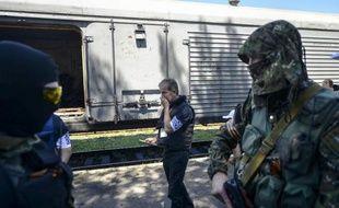 Des enquêteurs européens examinent les restes de corps de victimes du vol MH17 dans un train bloqué par les rebelles à Torez en Ukraine, le 21 juillet 2014