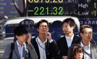 Des passants devant un tableau électronique affichant les cours de la Bourse, à Tokyo, le 14 octobre 2014