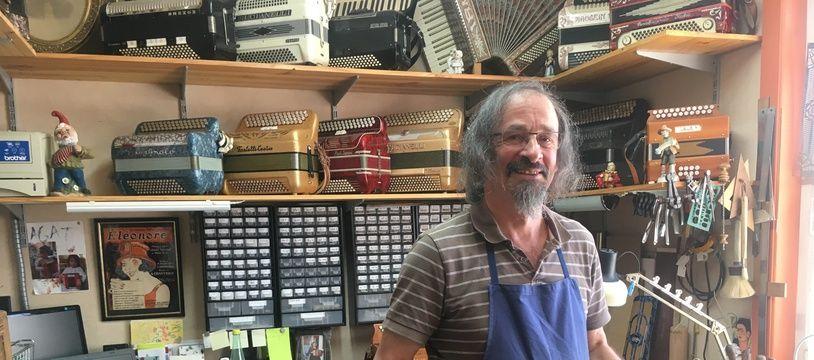 François Legris dans son atelier, portant un des accordéons qu'il est en train de réparer.