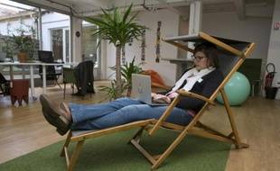 Une femme assise dans une chaise longue avec son ordinateur portable à l'espace de coworking Casaco de Malakoff, le 23 septembre 2015