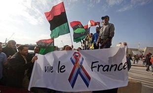 Des drapeaux de rebelles lybiens aux côtés d'une bannière française lors d'une manifestation le 23 mars 2011