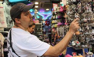 Cette fois encore, ce touriste brésilien de passage dans une boutique de souvenirs de la rue Rivoli se laisse tenter par une tour Eiffel miniature.