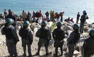 Des migrants attendent sur les rochers en bord de mer sous la surveillance de policiers, sur la frontière franco-italienne, à Vintimille, le 30 septembre 2015