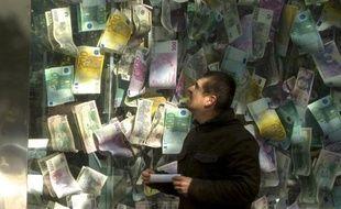 Un homme regarde une installation faite de billets de banques grand format, le 24 septembre 2013 à Prague