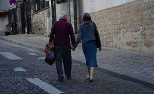 Un couple de personnes âgées main dans la main à Paris, le 14 avril 2020.