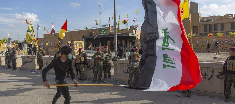 Un manifestant avec le drapeau irakien devant l'ambassade américaine de Bagdad, le 1er janvier 2020.