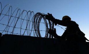 Un soldat américain retire, le 1er novembre 2014, des fils barbelés d'un mur d'enceinte de la base aérienne de l'Otan de Bagram, au nord de Kaboul