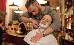 Laurent, le barbier des Faubourgs, s'occupe de la barbe du chanteur de Dionysos Mathias Malzieu, lors de la 7e édition du Paris Jazz Roots Dance Festival à La Bellevilloise, en avril 2013.