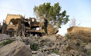 Un soldat dans lesruines d'une maison touchée par les raids de la coalition emmenée par l'Arabie Saoudite près de Sanaa, la capitale yéménite