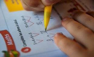 Un écolier de primaire qui fait un exercice de maths.