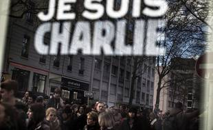 """A reflection in a urban placard reading """"Je suis Charlie"""" shows people during a Unity rally ìMarche Republicaineî on January 11, 2015 in Lyon in tribute to the 17 victims of the three-day killing spree in Paris area. The killings began on January 7 with an assault on the Charlie Hebdo satirical magazine in Paris that saw two brothers massacre 12 people including some of the country's best-known cartoonists and the storming of a Jewish supermarket on the eastern fringes of the capital which killed 4 local residents. A march with world leaders takes place through Paris in a historic display of global defiance against extremism after Islamist attacks that killed 17 victims in France. AFP PHOTO / JEFF PACHOUD"""