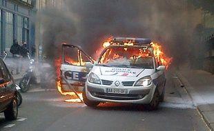 Photo prise par téléphone portable d'une voiture de police incendiée lors d'une contre-manifestation à Paris le 18 mai 2016