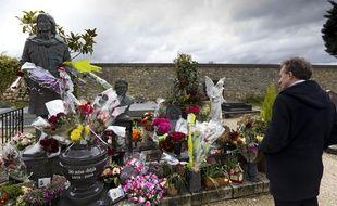 Le 17 mars 2013, un homme se recueille sur la tombe du chanteur Claude François qui a été vandalisée la veille dans le cimetière de Dannemois (Essonne).