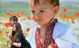 Un couple passe à Kiev le 23 mai 2014, devant une affiche d'un enfant portant la traditionnelle chemise ukrainienne, deux jours avant les élections présidentielles