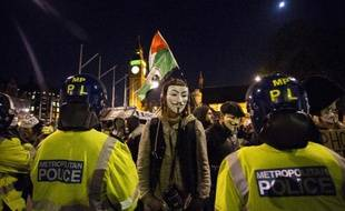 Des manifestants anticapitalistes, portant pour certains le masque des Anonymous, font face aux forces de l'ordre à Londres le 5 novembre 2014