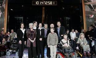 Television presenters Sophie Davant (front row standing, 2nd L), Olivier Minne (3rd L, back) and Nagui (C), President of AFM Laurence Tiennot Herment (4th L, standing) and French actors Gerard Jugnot (2nd R, standing) and Thierry Lhermitte (R, standing) celebrate the new record of 101.472.581 euros ($134,096,167), set during the 20th Telethon organised by the French Muscular Dystrophy Association (AFM), in Paris December 10, 2006. The annual fund raising event, which telecast live on French television for 30 hours, was staged to raise money for the research of genetic diseases in children. REUTERS/Benoit Tessier (FRANCE)