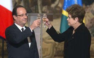 Le président François Hollande (G) et la présidente du Brésil Dilma Rousseff trinquent lors d'un dîner d'Etat à l'Elysée le 11 décembre 2012.
