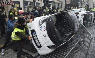 Des manifestants retournent une voiture aux abords des Champs-Elysées, lors de la mobilisation des