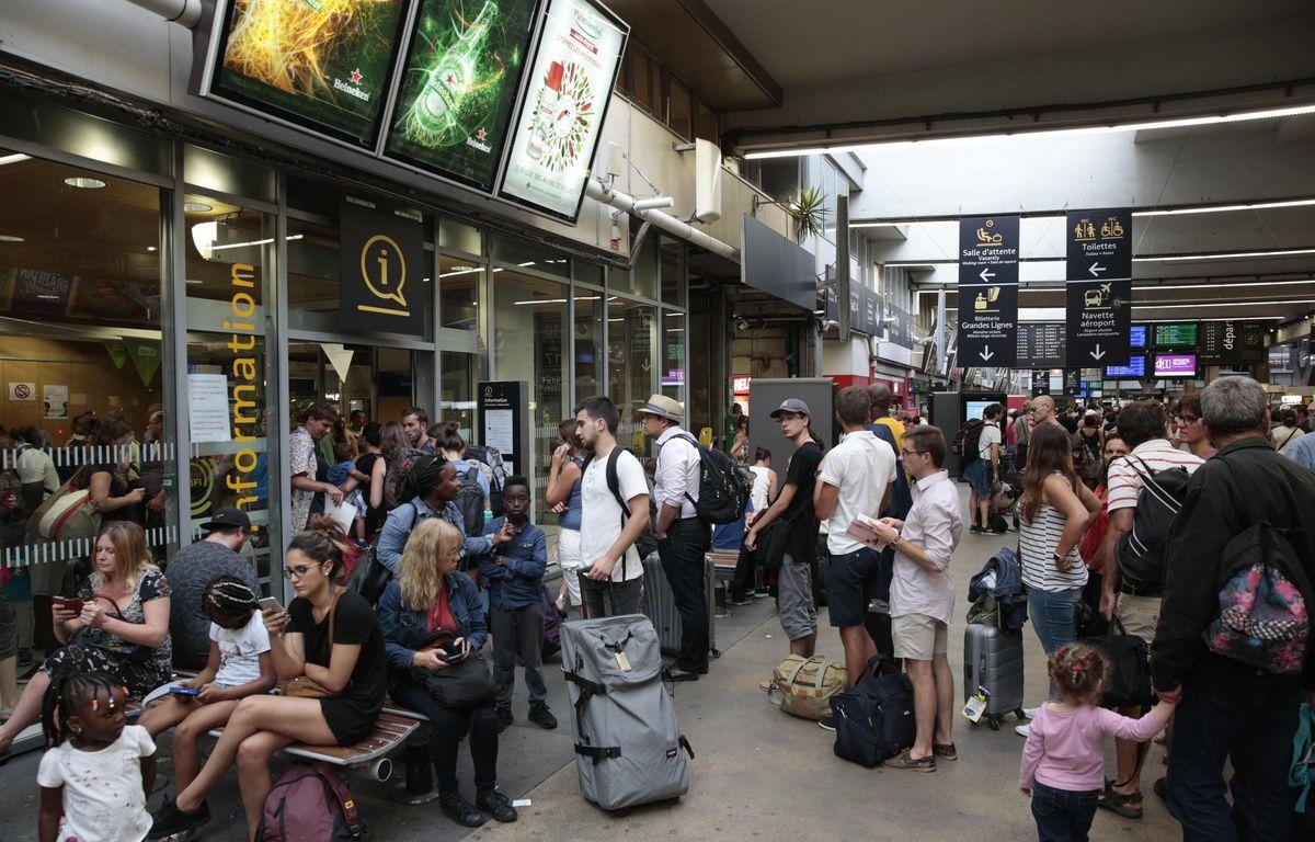 Des voyageurs patientaient déjà en gare de Paris-Montparnasse, le 17 juillet 2017, en raison d'une panne électrique. – AFP