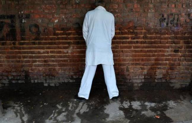 Un homme urine contre un mur dans une rue de New Delhi, le 18 novembre 2014, à la veille de la Journée mondiale des toilettes