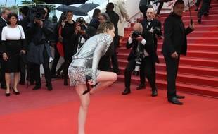 Kristen Stewart retirant ses chaussures sur le tapis rouge du Festival de Cannes.