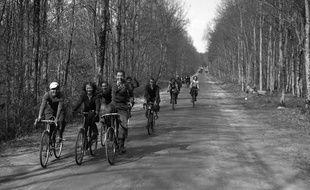 Des jeunes gens font une randonnée en bicyclette après avoir obten quinze jours de congés payés.