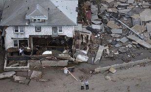 Deux hommes devant une maison détruite à Seagate, dans l'Etat de New York, aux Etats-Unis, le 31 octobre 2012.